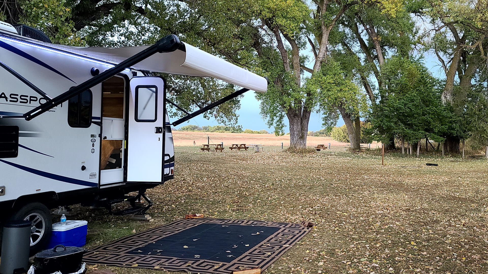 Camper with rug on the ground outside the door.