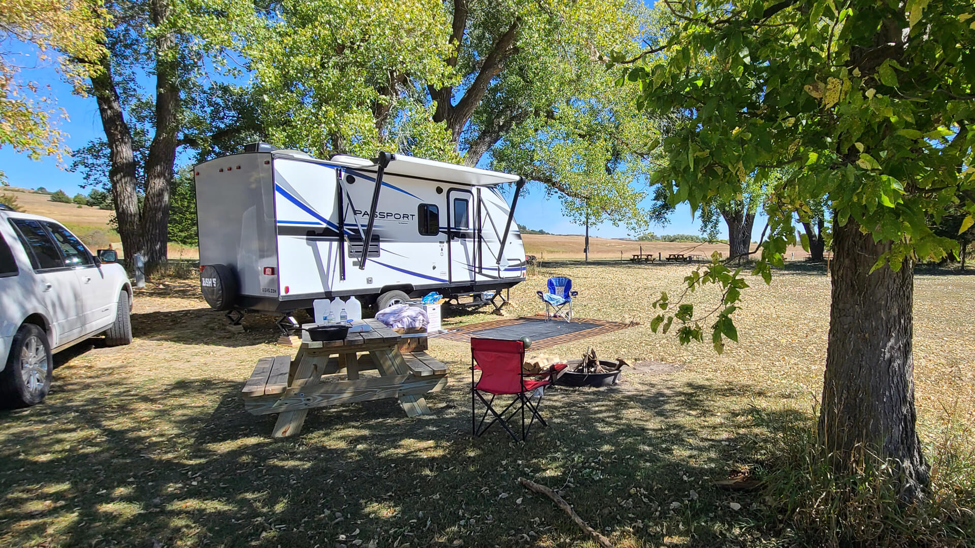 Camper set up near picnic table and fire pit