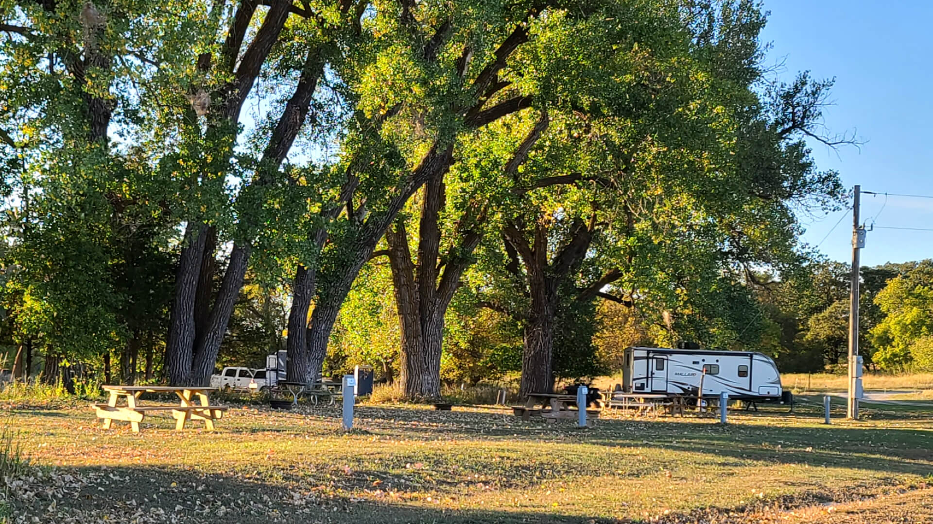 Open Camp Spot near the Niobrara River with camper in the background